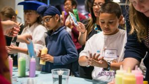 """Students learn how """"disease"""" spreads using colored water.  Photo from the Genentech archives."""